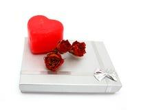 Geschenkkasten mit roter heart-shaped Kerze und Rosen stockbilder