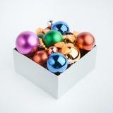 Geschenkkasten mit Weihnachtskugeln Stockbilder