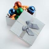Geschenkkasten mit Weihnachtskugeln Stockbild
