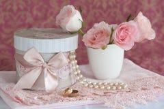 Geschenkkasten, Perlen, Hochzeitsringe und Rosen Stockfotografie