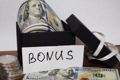 Geschenkpaket mit Dollar auf dem Tisch auf einem weißen Hintergrund, die Aufschrift Prämie stockfotos
