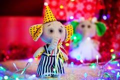Geschenkspielzeugelefant im gelben Kappenstand auf Hintergrund von Weihnachtslichtern und -kästen Lizenzfreies Stockfoto