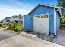 Geschermde binnenplaats met gras gevulde tuin en kleine blauwe loods Stock Foto
