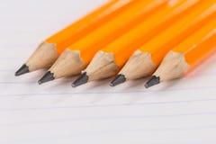 Gescherpte potloden die op een notitieboekjeblad in een strook liggen royalty-vrije stock foto