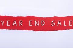 Gescheurd document met een woord van de EIND VAN HET JAARverkoop op rode achtergrond Stock Foto's