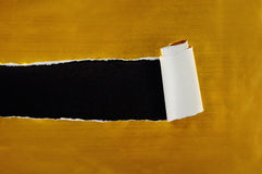 Gescheurd gouden document tegen een zwarte achtergrond Royalty-vrije Stock Foto