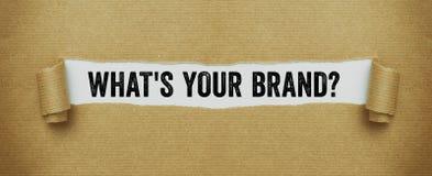 Gescheurd pakpapier die de woorden openbaren wat uw merk is stock foto