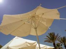 Gescheurde die strandparaplu door de zon tegen de hemel wordt aangestoken Stock Afbeeldingen