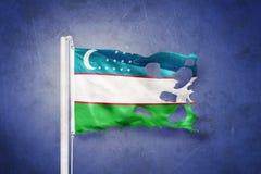 Gescheurde vlag die van Oezbekistan tegen grungeachtergrond vliegen Stock Foto's