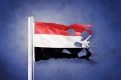 Gescheurde vlag die van Yemen tegen grungeachtergrond vliegen Stock Foto