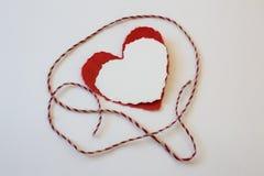 Gescheurde witte en rode valentijnskaartharten met rode en witte streng Royalty-vrije Stock Afbeelding