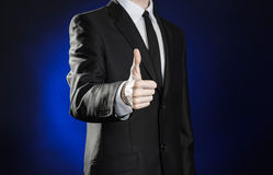 Geschäft und die Darstellung des Themas: bemannen Sie in einem schwarzen Anzug, der Handzeichen auf einem dunkelblauen Hintergrun Stockfotografie