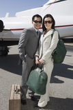 Geschäfts-Paare, die zusammen am Flugplatz stehen Lizenzfreie Stockfotografie