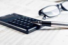 Geschäftsfüllfederhalter, -taschenrechner und -gläser auf Finanzdiagramm Stockbilder