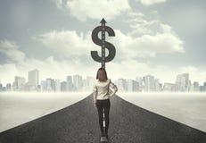 Geschäftsfrau auf Straßenüberschrift in Richtung zu einem Dollarzeichen Lizenzfreies Stockfoto