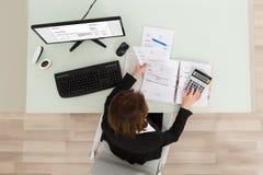 Geschäftsfrau Calculating Financial Report Lizenzfreie Stockfotos