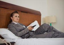 Geschäftsfrau, die auf Bett und aufpassendes Fernsehen legt Lizenzfreies Stockbild