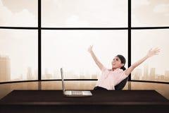 Geschäftsfrau, die auf dem Stuhl mit der Erhöhungshand und -laptop sitzt Stockbild