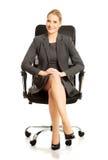 Geschäftsfrau, die auf Lehnsessel sitzt Stockbilder