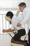 Geschäftsfrau, die auf Massagestuhl sitzt, Lizenzfreie Stockbilder