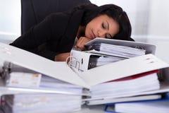 Geschäftsfrau, die auf Stapel von Ordnern schläft Stockbild