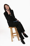 Geschäftsfrau, die auf Stuhl sitzt und auf aufrufendes Programm hört Stockbild