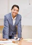 Geschäftsfrau, die auf Tabelle im Konferenzsaal sich lehnt Lizenzfreies Stockbild
