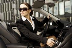 Geschäftsfrau, die ein Auto antreibt Stockfotografie
