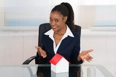 Geschäftsfrau, die ein Hausmodell darstellt Stockbilder