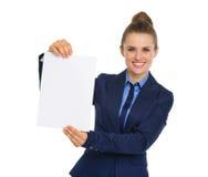 Geschäftsfrau, die ein leeres Blatt Papier lächelt und hält Lizenzfreie Stockbilder