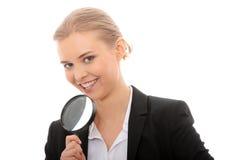 Geschäftsfrau, die ein Vergrößerungsglas untersucht Stockfoto