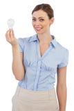 Geschäftsfrau, die eine Glühlampe hält Lizenzfreie Stockfotografie