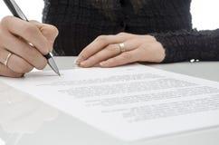 Geschäftsfrau, die einen Vertrag über Unterzeichnungszeile unterzeichnet Stockfoto