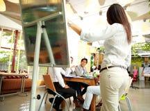 Geschäftsfrau, die etwas auf einer Sitzung darstellt Stockfoto
