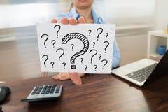 Geschäftsfrau, die Fragezeichenzeichen zeigt Stockfotos