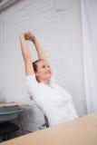 Geschäftsfrau, die Hände im Büro ausdehnt Lizenzfreies Stockbild