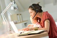 Geschäftsfrau, die ihr Baby hält und an Laptop arbeitet Lizenzfreie Stockfotografie