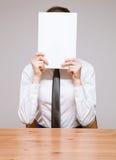 Geschäftsfrau, die ihr Gesicht hinter Dokumenten versteckt Stockbild