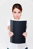 Geschäftsfrau, die ihren Report im schwarzen Faltblatt zeigt Stockbild