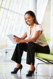 Geschäftsfrau, die im modernen Büro unter Verwendung Digital-Tablette sitzt Stockfotografie