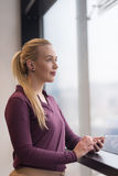 Geschäftsfrau, die intelligentes Telefon im Büro verwendet Stockfotos