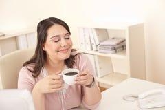 Geschäftsfrau, die Kaffee im modernen Büro genießt Lizenzfreies Stockbild