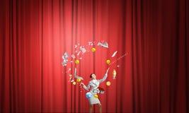 Geschäftsfrau, die mit Bällen jongliert Stockfoto