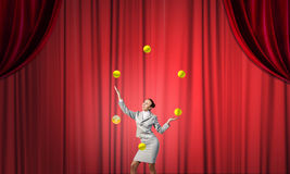 Geschäftsfrau, die mit Bällen jongliert Lizenzfreie Stockbilder