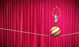 Geschäftsfrau, die mit Bällen jongliert Stockbilder