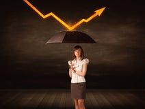 Geschäftsfrau, die mit dem Regenschirm hält orange Pfeil steht Stockfotos
