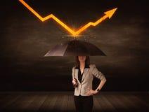 Geschäftsfrau, die mit dem Regenschirm hält orange Pfeil steht Stockfotografie