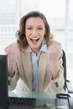 Geschäftsfrau, die mit den geballten Fäusten im Büro zujubelt Stockfotos