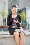 Geschäftsfrau, die mit Telefon isst und arbeitet Stockbilder