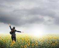 Geschäftsfrau, die in rainclouds über Sonnenblumenfeld springt Lizenzfreies Stockfoto